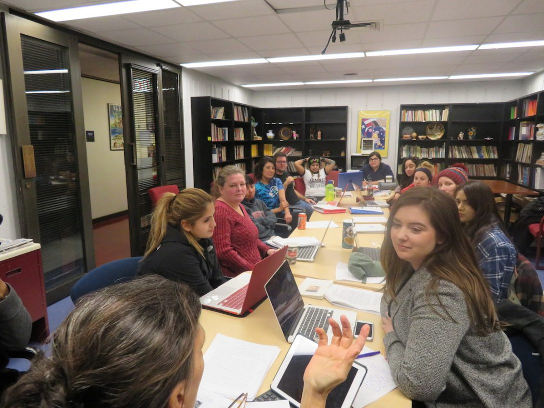 Graduate seminar with students engaged in discussion with instructor